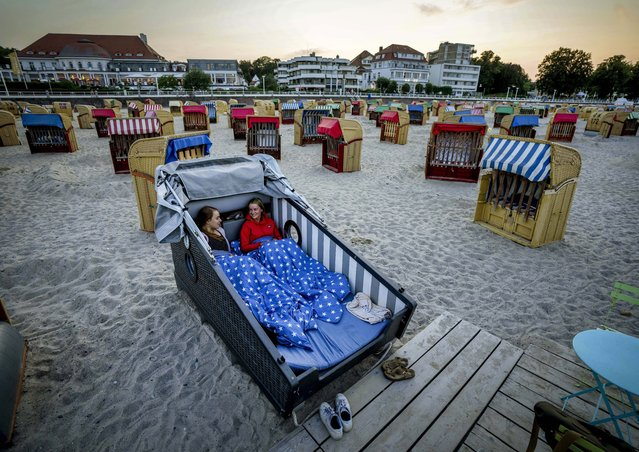 Two young women prepare to spend the night in a specially designed beach chair at the beach of the Baltic Sea in Travemuende, Germany, Sunday, July 18, 2021. A hotel owner offers that special accommodation for the first time at German beaches. (Photo by Michael Probst/AP Photo)