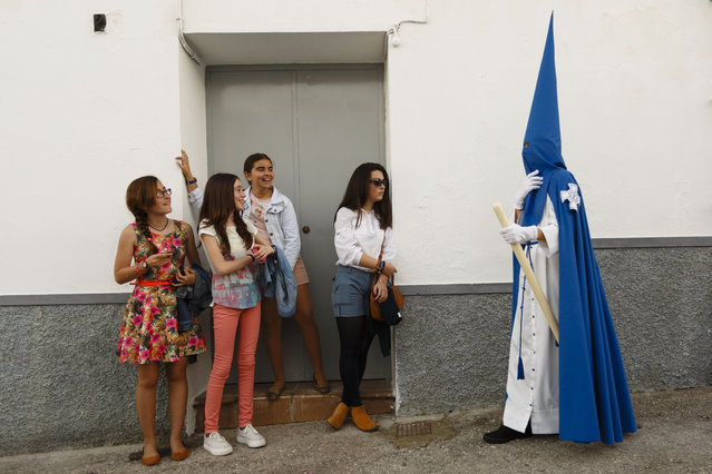 "Girls look at a penitent taking part in ""Nuestro Senor Atado a la Columna, Maria Santisima de la Paz y San Juan Evangelista"" Holy Week procession in Arcos de la Frontera, Spain, Tuesday, March 31, 2015. Hundreds of processions take place throughout Spain during the Easter Holy Week. (Photo by Daniel Ochoa de Olza/AP Photo)"