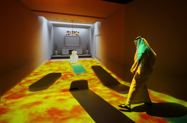 """An Emirati man plays at the """"Caring Machines"""" section of the Museum of the future during the opening day of the World Government Summit in Dubai, United Arab Emirates, Monday, February 8, 2016. Those gathered for the World Government Summit in Dubai offered no immediate solutions to the crises gripping the region, like low global oil prices, global warming and the rise of violent extremism. But all acknowledged that keeping government responsive to its citizens remains crucial. (Photo by Kamran Jebreili/AP Photo)"""