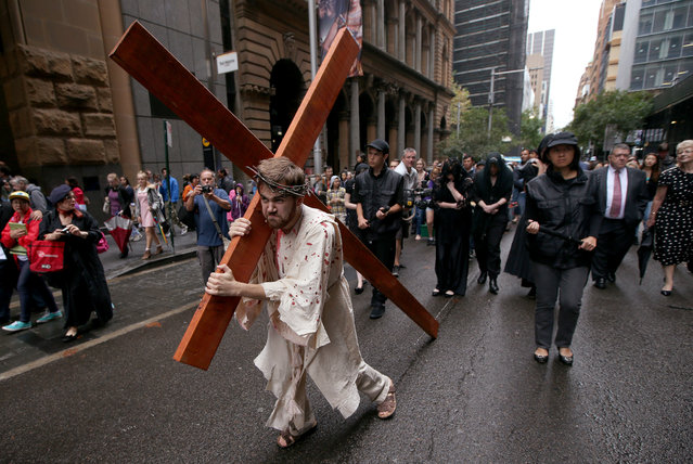 Brendan Paul plays the part of Jesus during a re-enactment of the crucifixion of Christ in Sydney, Friday, April 3, 2015. Members of the Wesley Mission use a modern interpretation of the recreation of Jesus' journey to the cross before a Good Friday service is held. (Photo by Rick Rycroft/AP Photo)