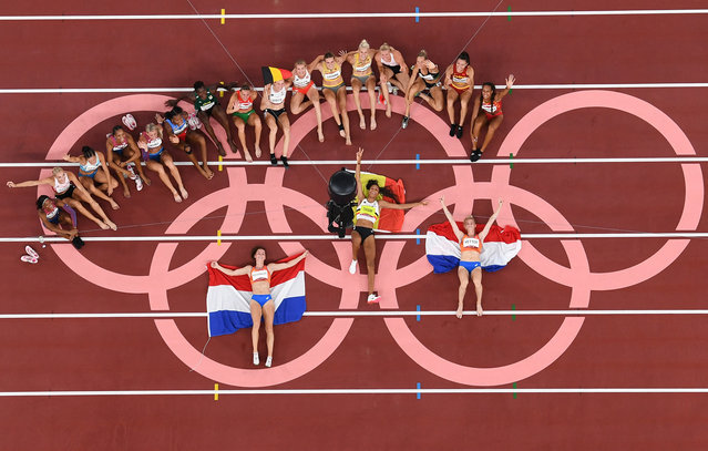 An overview shows Gold medallist Belgium's Nafissatou Thiam (C), silver medallist Netherlands' Anouk Vetter (R) and bronze medallist Netherlands' Emma Oosterwegel as they pose after the women's heptathlon event during the Tokyo 2020 Olympic Games at the Olympic Stadium in Tokyo on August 5, 2021. (Photo by Antonin Thuillier/AFP Photo)