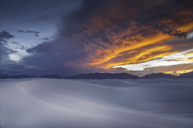 """""""Fire in the sky"""". I took this photo at sunset in September at White Sands, New Mexico. It was a beautiful evening with the light changing as it got closer to sunset, but none of us expected the magnificent orange sky that appeared immediately after the sun set. Photo location: White Sands National Monument. (Photo and caption by Chris Gattuso/National Geographic Photo Contest)"""