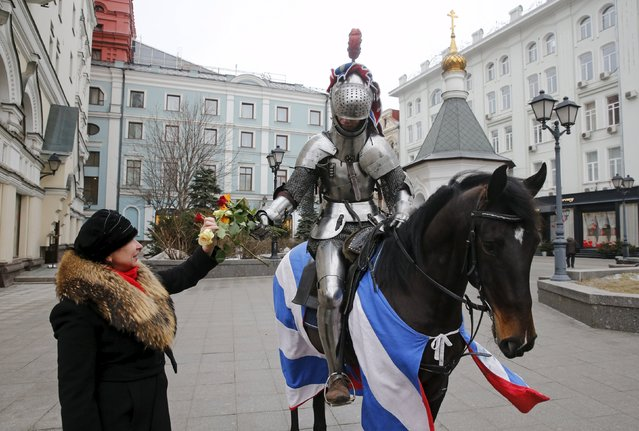 A participant, riding a horse and dressed as a knight, presents flowers to women during an event marking Valentine's Day in central Moscow, Russia, February 14, 2016. (Photo by Maxim Zmeyev/Reuters)