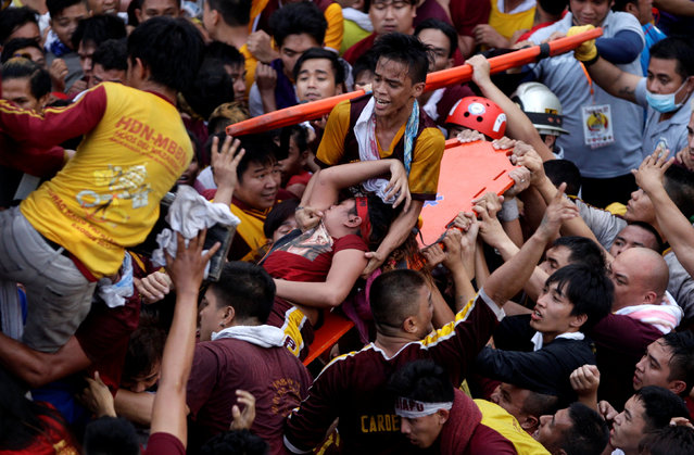 Devotees carry a woman who fainted while taking part in the annual procession of the Black Nazarene in Manila, Philippines January 9, 2017. (Photo by Czar Dancel/Reuters)