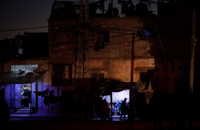 A Palestinian walks past a makeshift vegetable shop lit with a lamp powered by a battery during a power cut in Beit Lahiya in the northern Gaza Strip January 11, 2017. (Photo by Mohammed Salem/Reuters)