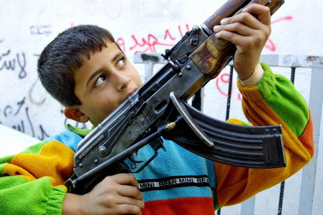 A Palestinian boy holds a gunman's AK-47 assault rifle during a round of fighting with Israeli soldiers October 26, 2001 in the al-Azzar refugee camp located within the West Bank town of Bethlehem. (Photo by David Silverman/Getty Images)