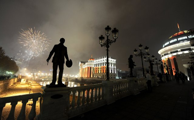 Silhouettes of sculptures are seen on a bridge, as fireworks explode over Vardar River during New Year's Eve celebration in Skopje, Macedonia, Wednesday, January 1, 2014. (Photo by Boris Grdanoski/AP Photo)