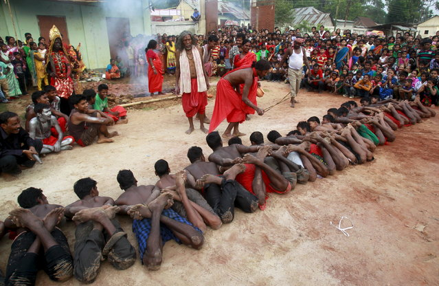 A Hindu priest (C) blesses ritually bound devotees lying on the ground during a ritual as part of the annual Shiva Gajan religious festival at Pratapgarh, on the outskirts of Agartala, April 14, 2015. (Photo by Jayanta Dey/Reuters)