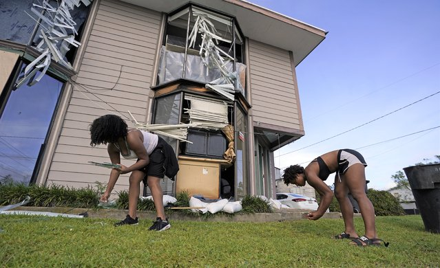 Corieon Austin, right, and Victoria Simmons pick up broken glass in the aftermath of Hurricane Ida, Monday, August 30, 2021, in Houma, La. (Photo by David J. Phillip/AP Photo)