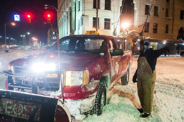 Leroy Griffis, a maintenance supervisor for the Flint Downtown Development Authority, directs a snowplow to an assignment where he will clear streets at about 6:10 a.m., Monday, January 6, 2014, in downtown Flint, Mich., where a recorded 16.2 inches of snow fell. (Photo by Jake May/AP Photo/The Flint Journal-MLive.com)