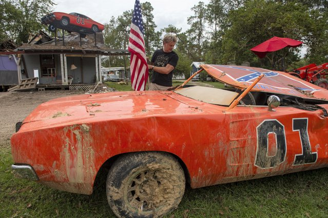 """Actor John Schneider, who starred in the television show """"The Dukes of Hazzard"""", places an American flag on his """"General Lee"""" car on Monday, September 6, 2021, that was destroyed by Hurricane Ida. The car was made famous during the show which aired in the early eighties. (Photo by Chris Granger/AP Photo)"""