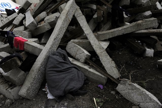 A refugee sleeps next to debris at a makeshift camp set up by stranded refugees and migrants who are waiting to cross the Greek-Macedonian border, near the Greek village of Idomeni, February 29, 2016. (Photo by Alexandros Avramidis/Reuters)