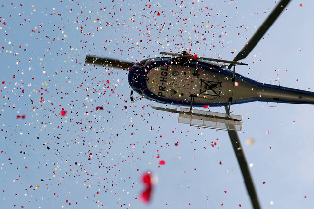 A helicopter showers flowers in honor of victims of the collapse of a dam owned by Brazilian mining company Vale SA, in Brumadinho, Brazil February 25, 2019. (Photo by Washington Alves/Reuters)