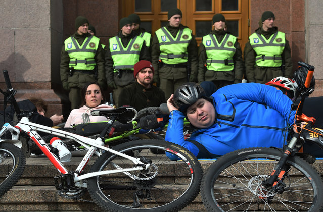 Bicyclists take part in the die-in action in front of the city hall of the Ukrainian capital Kiev on March 14, 2019 to ask modern infrastructure for safe cycling traffic. The protesters demand modern infrastructure for safe cycling traffic in the city and severely punish drivers who ignore cyclists on the road. (Photo by Sergei Supinsky/AFP Photo)