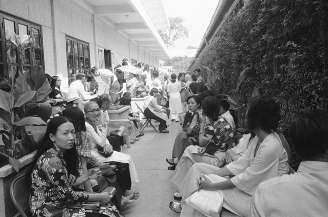 The line of Americans and their Vietnamese dependents grows larger at the U.S. consulate in Saigon, April 18, 1975 where many seek papers to emigrate. This picture, taken Friday morning shows a portion of the hundreds who appear daily at the mission. (Photo by Nick Ut/AP Photo)