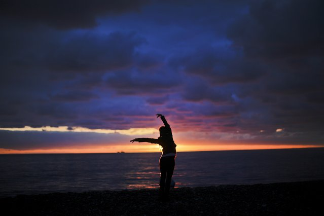 Elina Suyundikova, a dancer in the 2014 Winter Olympics opening ceremony, watches the sunset along the Black Sea while returning from a rehearsal on the eve of the performance and the games' official opening, Thursday, February 6, 2014, in Sochi, Russia. (Photo by David Goldman/AP Photo)