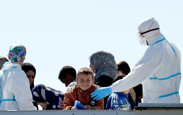 An Italian naval officer interacts with a child amongst rescued migrants onboard the Italian Navy vessel Bettica as they arrive in the Sicilian harbour of Augusta on April 22, 2015. (Photo by Alberto Pizzoli/AFP Photo)