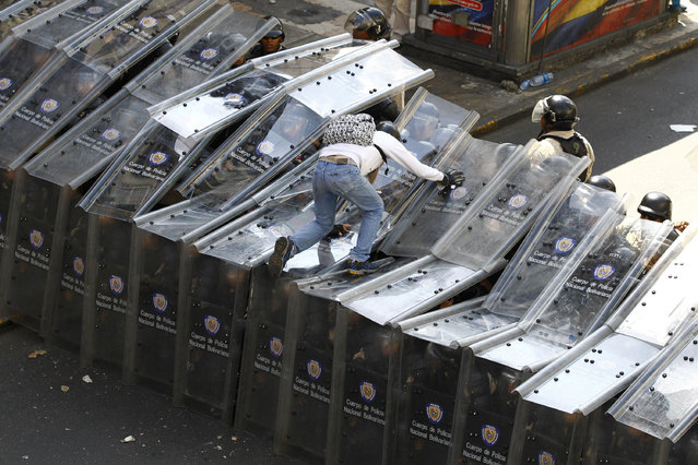 A demonstrator jumps on shield wall formed by riot police during a protest against Venezuela's President Nicolas Maduro's government in Caracas February 12, 2014. One person (not pictured) was killed during standoffs at the end of the anti-government rally in Caracas on Wednesday, witnesses said, escalating the worst bout of unrest in Venezuela since protests against Maduro's April 2013 election. (Photo by Carlos Garcia Rawlins/Reuters)