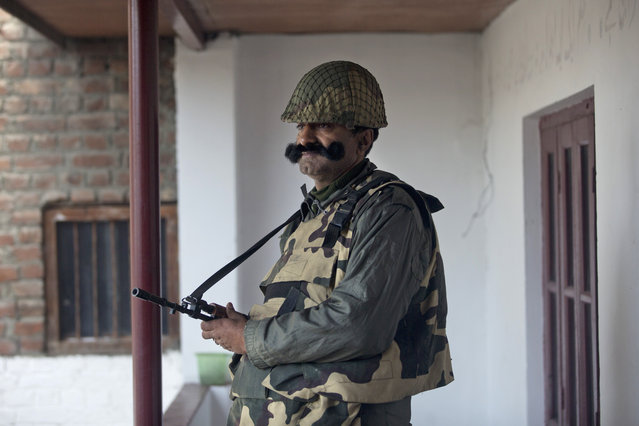 An Indian paramilitary soldier stands guard at a polling station during the second phase of India's general elections, in Srinagar, Indian controlled Kashmir, Thursday, April 18, 2019. Kashmiri separatist leaders who challenge India's sovereignty over the disputed region have called for a boycott of the vote. Most polling stations in Srinagar and Budgam areas of Kashmir looked deserted in the morning with more armed police, paramilitary soldiers and election staff present than voters. (Photo by Dar Yasin/AP Photo)
