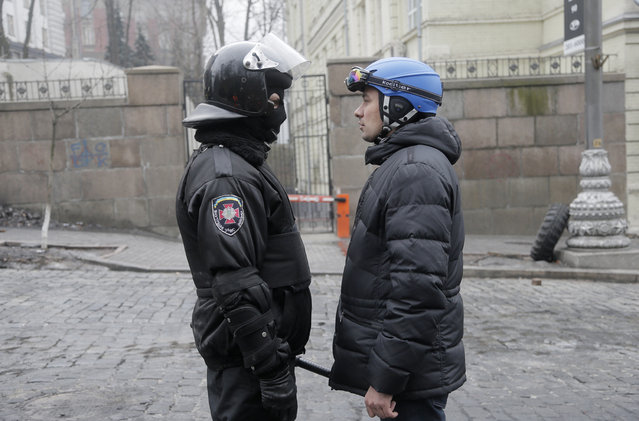 A high-ranking police officer, left, and a protester representative hold talks near the Cabinet of Ministers in Kiev, on February 20, 2014. (Photo by Efrem Lukatsky/AP Photo)