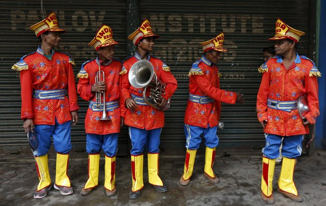 Local band members wait to board a passenger bus to reach a wedding procession venue in Kolkata, India, March 10, 2016. (Photo by Rupak De Chowdhuri/Reuters)