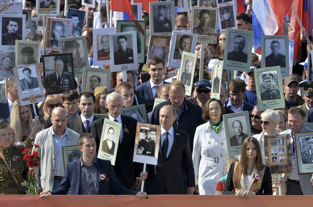 Russian President Vladimir Putin (C) holds the portrait of his father as he takes part in the Immortal Regiment march with pictures of World War Two soldiers on Red Square during the Victory Day celebrations in Moscow, Russia, May 9, 2015. (Photo by Reuters/Host Photo Agency/RIA Novosti)