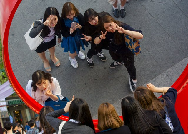 A group of girls pose for their friend in a large mirror in the Sinchon district in Seoul, May 5, 2015. (Photo by Thomas Peter/Reuters)