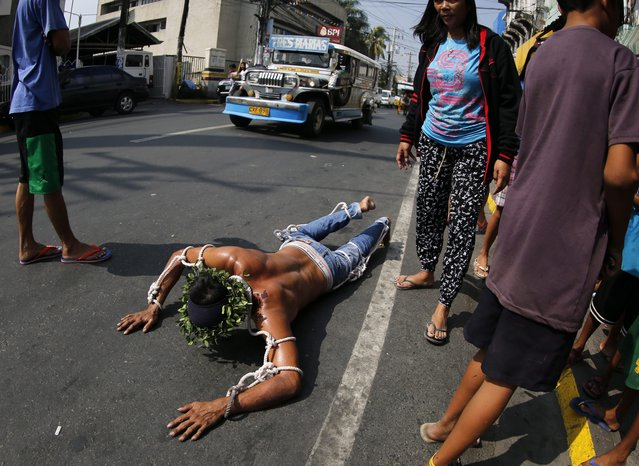 A Filipino flagellant crawls along a street on Maundy Thursday, in San Fernando city, Pampanga Province, north of Manila, Philippines, 24 March 2016. Many Filipino Catholic penitents mark the Holy Week by submitting to different forms of physical penance in the hopes of being forgiven for their sins. (Photo by Francis R. Malasig/EPA)