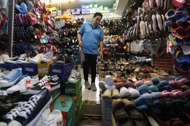 A Thai customer looks for shoes in Bangkok, Thailand, Thursday, March 28, 2019. As Thais wait for official results of their general election, political parties led by one ousted from power in a military coup say they believe they have won enough seats to form the next government. (Photo by Sakchai Lalit/AP Photo)
