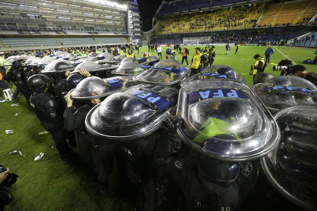 Riot police hold up their shields to make a corridor for River Plate players exit the stadium after their  Copa Libertadores soccer match with Boca Juniors was suspended after the first half in Buenos Aires, Argentina, Friday, May 15, 2015. Police are investigating after the high-profile match was stopped when visiting players were sprayed by fans with an eye irritant believed to be pepper spray or mace. (Photo by Victor R. Caivano/AP Photo)