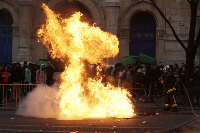 """French firemen try to extinguish burning dustbins as students gather during a demonstration against police brutality, following the alleged rape of Theo, outside the """"Lycee Voltaire"""" secondary school in Paris, on February 23, 2017. (Photo by Geoffroy van der Hasselt/AFP Photo)"""