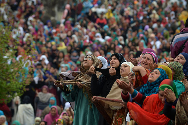 Indian Kashmiri Muslims pray before a priest shows a relic believed to be hair from the beard of Prophet Muhammed during special prayers on the death anniversary of Abu Bakr Siddiq, the first Caliph of Islam at the Hazratbal Shrine in Srinagar on April 1, 2016. Thousands of Kashmiri Muslims gathered at the shrine in the summer capital of Jammu and Kashmir to offer special prayers. (Photo by Tauseef Mustafa/AFP Photo)