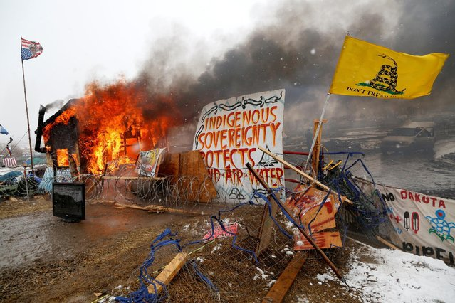 A structure burns after being set alight by protesters preparing to evacuate the main opposition camp against the Dakota Access oil pipeline near Cannon Ball, North Dakota, U.S., February 22, 2017. (Photo by Terray Sylvester/Reuters)