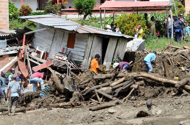 Residents remove mud and debris as they search for bodies after a landslide in the municipality of Salgar, in Antioquia department May 18, 2015. A landslide sent mud and water crashing onto homes in a town in Colombia's northwest mountains on Monday, killing at least 50 people and injuring dozens, officials said. (Photo by Reuters/Stringer)