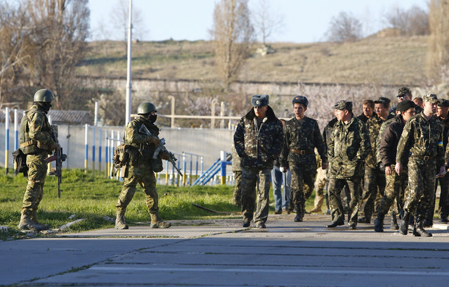 Armed men (L), believed to be Russian servicemen, stand guard as Ukrainian servicemen pass by at a military airbase in the Crimean town of Belbek near Sevastopol March 22, 2014. The commander of Belbek airbase in Crimea said on Saturday he would be taken away by Russian forces for talks after they entered the base with armored vehicles and automatic rifles. (Photo by Shamil Zhumatov/Reuters)
