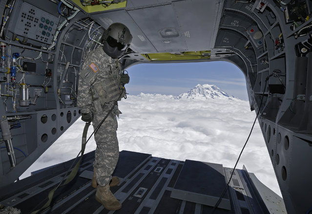 In this photo taken May 15, 2015, U.S. Army Reserve Staff Sgt. Ryan Elkins, a flight engineer, stands near the open rear door of a Boeing CH-47F Chinook helicopter as it flies near Mount Rainier in Washington state to give members of the media a view of mountain search and rescue training exercises involving another CH-47F. (Photo by Ted S. Warren/AP Photo)
