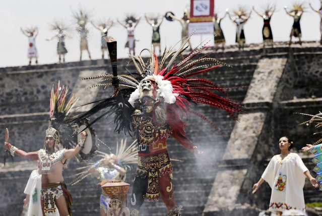 Dancers dressed in prehispanic costumes perform during the Ceremony of the Ignition of the New Fire, at the ancient pyramids of Teotihuacan outside Mexico City May 25, 2015. The flame will be transferred to Toronto for the Pan-American games, which will be held there from July 10 to 26. (Photo by Henry Romero/Reuters)