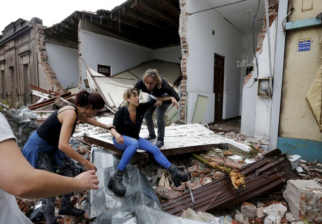 A woman is helped by others amidst debris at a street in Dolores, the day after the city was hit by a tornado, April 16, 2016. (Photo by Andres Stapff/Reuters)