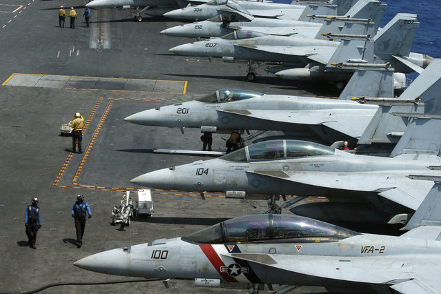 A row of F18 fighter jets on the deck of the U.S. Navy aircraft carrier USS Carl Vinson (CVN 70) is prepared for patrols off the disputed South China Sea Friday, March 3, 2017. (Photo by Bullit Marquez/AP Photo)