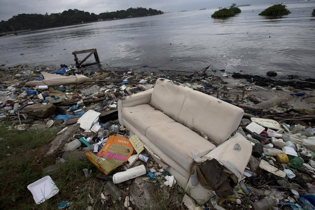 A sofa litters Guanabara Bay along with other trash in Rio de Janeiro, Brazil, Monday, June 1, 2015. Art students at a Rio de Janeiro university have taken advantage of a material they have in endless supply trash to create an exhibition that aims to draw attention to the fetid state of the city's Guanabara Bay, where the Olympic sailing events are to be held next year. (AP Photo/Silvia Izquierdo)