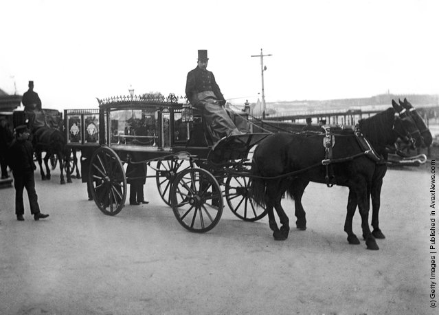 Pallbearers attend a glass sided funeral carriage in Portsmouth, circa 1900