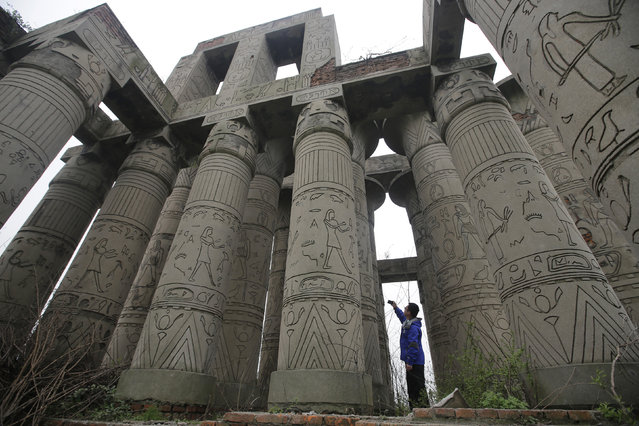A visitor takes a photograph of a carved structure, which is a replica of the Karnak Temple in Egypt, at the abandoned Wanguo park in Wuhan, Hubei province March 12, 2013. The park was abandoned during the course of construction 14 years ago, according to local media. (Photo by Reuters/Stringer)