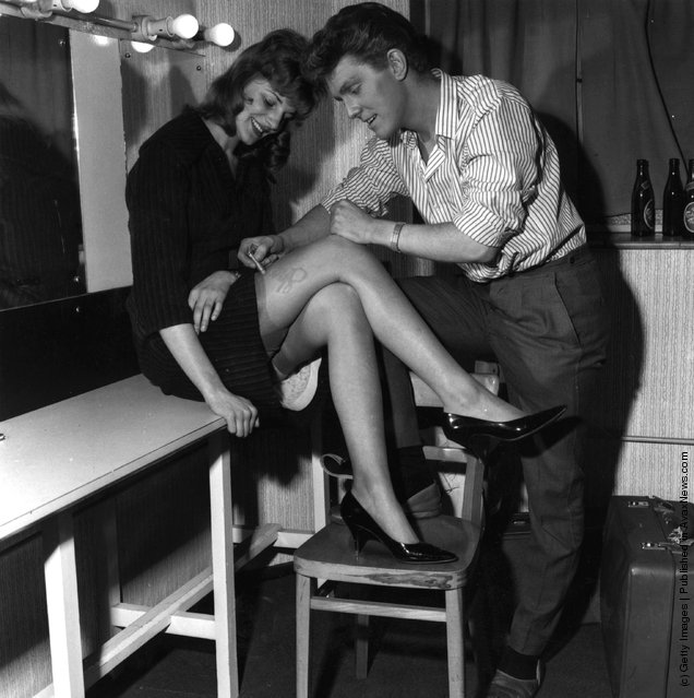 1962: English pop singer Shane Fenton, later known as Alvin Stardust, autographing a woman's leg in his dressing room