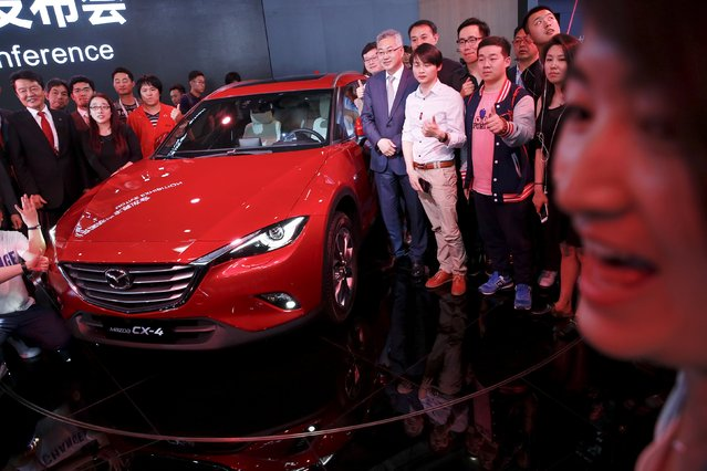 People have their pictures taken next to a newly unveiled Mazda CX-4 during the Auto China 2016 auto show in Beijing April 25, 2016. (Photo by Damir Sagolj/Reuters)