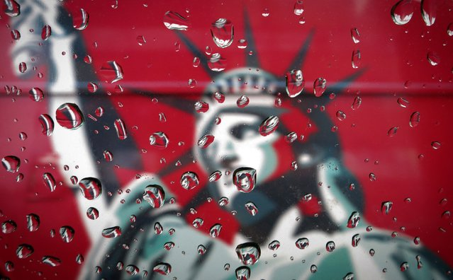 An image of the Statue of Liberty is pictured though a rain covered taxi window in New York April 15, 2014. (Photo by Carlo Allegri/Reuters)