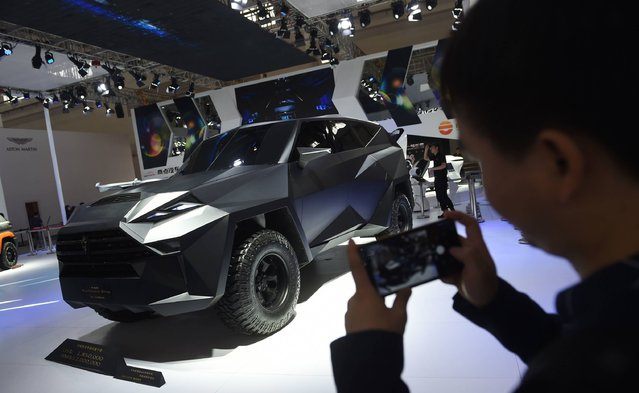 A man photographs a Karlmann King at the Beijing Auto Show in Beijing on April 26, 2016. The German made vehicle sells for 1,850,000 USD. The show is the premier annual event for carmakers to present their latest models in China, the world's biggest auto market. (Photo by Greg Baker/AFP Photo)