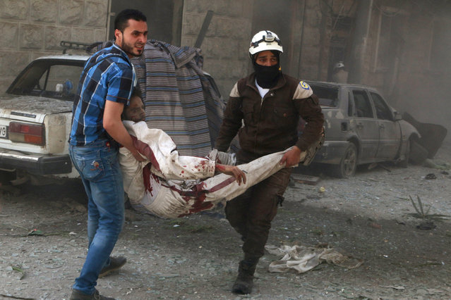 Civil defense members carry an injured civilian at a site hit by airstrikes in the rebel held area of Aleppo's al-Fardous district, Syria, April 29, 2016. (Photo by Abdalrhman Ismail/Reuters)