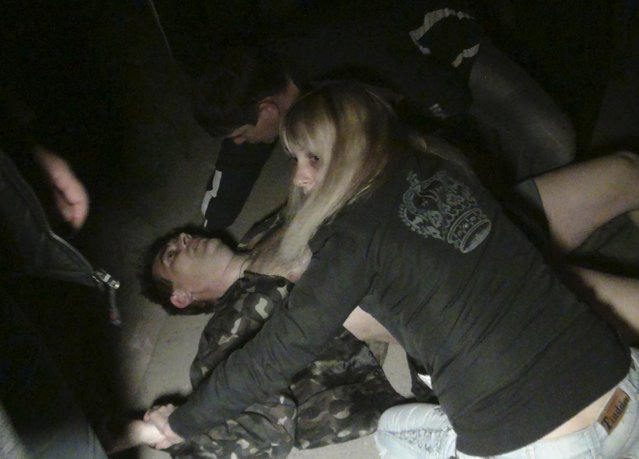 """People surround a man who was injured during pro-Russian protests near a Ukrainian military base in Mariupol, on April 16, 2014. Ukraine's interior minister said on Thursday that three pro-Russian separatists were killed in shooting that broke out overnight in the town of Mariupol on the Sea of Azov. """"According to preliminary data, three attackers were killed, 13 wounded and 63 detained"""". Arsen Avakov said in a post on Facebook. (Photo by Reuters/Stringer)"""