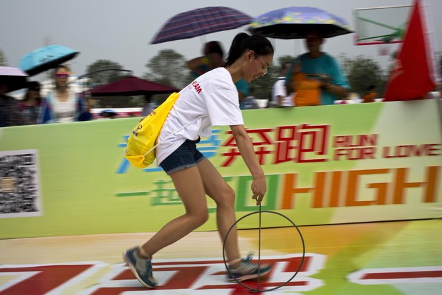 A woman plays rolling iron hoop during a public sport campaign to promote exercise organized by city government at Garden Expo Park in Beijing, China, Sunday, June 28, 2015. The campaign is to encourage people exercise to support Beijing's bid to host the 2022 Winter Olympics. (Photo by Andy Wong/AP Photo)