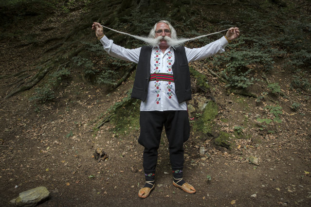 Zoran Lazarevic, 70-years-old, shows off his moustache as he takes part in the longest moustache competition at the 15th century Kalenic Serbian Orthodox monastery, near Rekovac, central Serbia on August 4, 2019. Lazarevic won the competition with his 140 centimetre long moustache. (Photo by Vladimir Zivojinovic/AFP Photo)